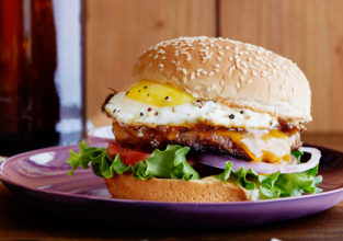 FNK HANGOVER BREAKFAST SAUSAGEANDEGG BURGER Food Network Kitchen Food Network Mayonnaise, Sriracha, Maple Syrup, Hamburger Bun, Lettuce, Tomato, Breakfast Sausage, Red Onion, Cheddar Cheese, Egg
